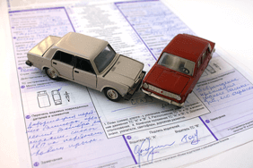 Two toy cars crashing on paperwork