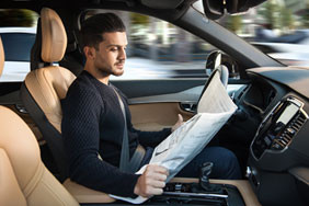 Driver reading newspaper while driving