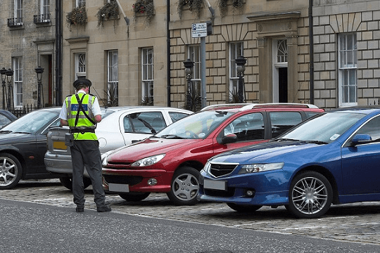 A traffic warden stood in front of a row of cars