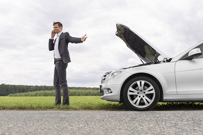 Man on phone next to broken down car