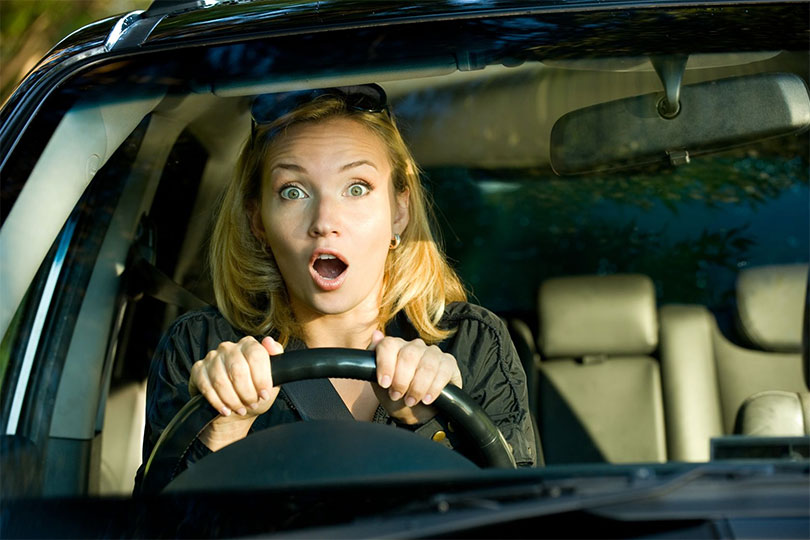 Woman looking scared at the wheel