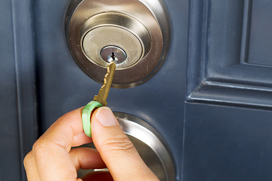 female putting key in lock