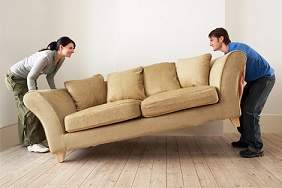 Couple moving a sofa