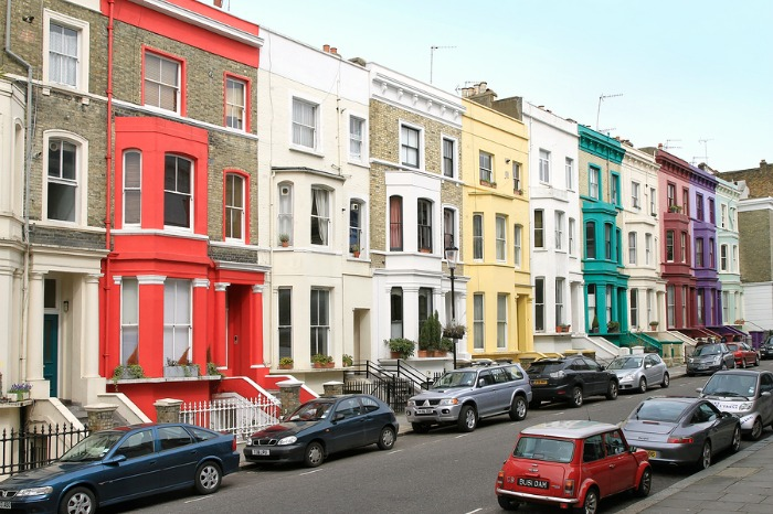 A residential street in London with lots of cars parked on it