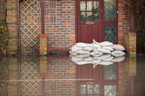 A flooded house with sandbags in front