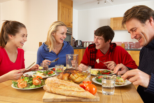 Teenagers eating a meal with the family