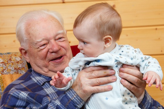 An old man holding a little baby