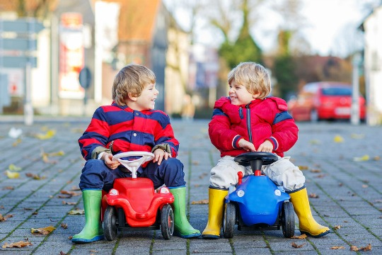 Two little boys wrapped up warm on ride-on tractors