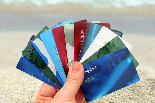 A hand holding fanned out credit cards, on the beach
