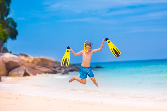 Kid on a beach with flippers jumping in the air